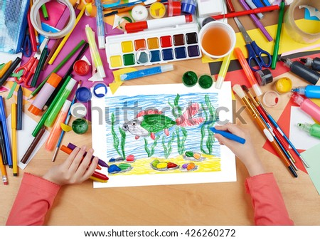 big fish under water child drawing, top view hands with pencil painting picture on paper, artwork workplace - stock photo