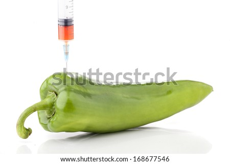 Big fresh green paprika with a syringe. Concept for genetically modified foods. - stock photo