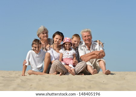 big friendly family relaxing on the sand together in the summer - stock photo