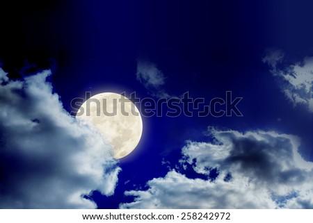 Big full moon is behind the cloud in dark sky, as background - stock photo