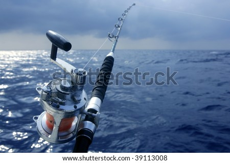 Big game boat fishing in deep sea on boat under cloudy winter time - stock photo