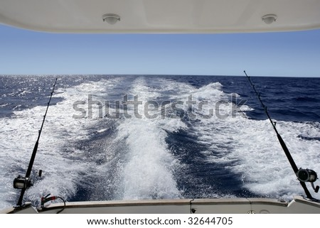Big game boat fishing ocean sea, with prop wash, two rod and reel - stock photo