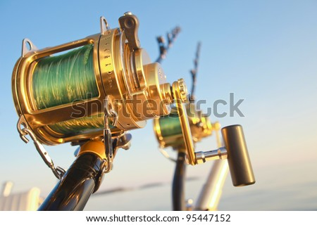 big game fishin reels and rods lit by setting sun - stock photo
