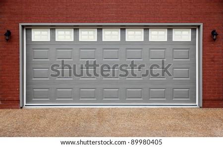 Big garage with gray doors, brick wall and asphalt driveway - stock photo