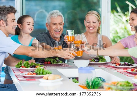 big generation family, parents, children and grandparents, drink orange juice toast happy smile lunch dinner at table, home - stock photo