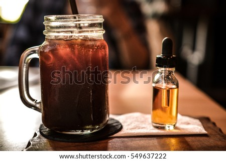 big glass of ice tea and small bottle of syrup