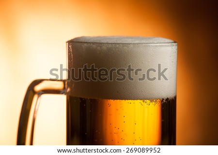 Big glass with handle filled with fresh beer with a lot of foam on top on brown background - stock photo