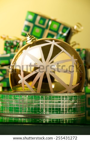 big gold xmas ball with snowflake placed on green and gold tinsel against green and gold xmas gifts  - stock photo