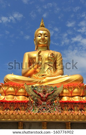 Big  golden Buddha statue on blue sky background - stock photo
