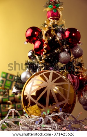 big golden xmas ball with snowflake placed on xmas color lights  , xmas tree for background  - stock photo