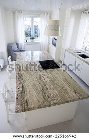 Big granitic worktop in bright kitchen, vertical - stock photo