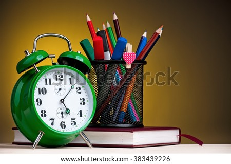 Big green alarm clock with notepad, black holder and pencils on dark yellow background - stock photo