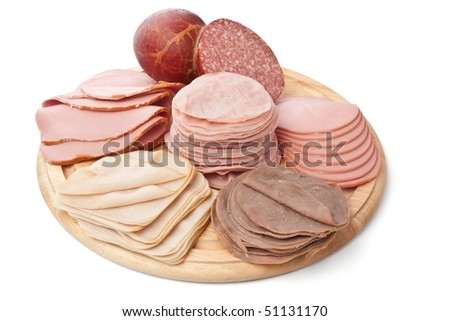 big group of meat on a round wooden board - stock photo