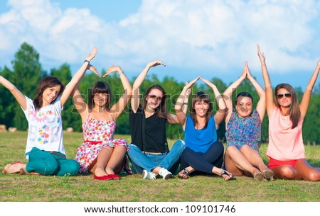 Big group of young girls with hands up