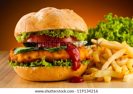 Big hamburger, chicken nuggets and French fries - stock photo