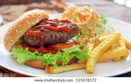 Big Hamburger topping with tomato sauce serve with fries and salad - stock photo