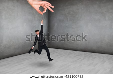 Big hand holds businessman in rough room
