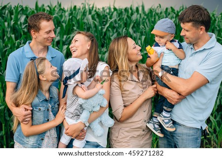 big handsome happy family standing having fun in the cornfield. Little girl with teddy bear