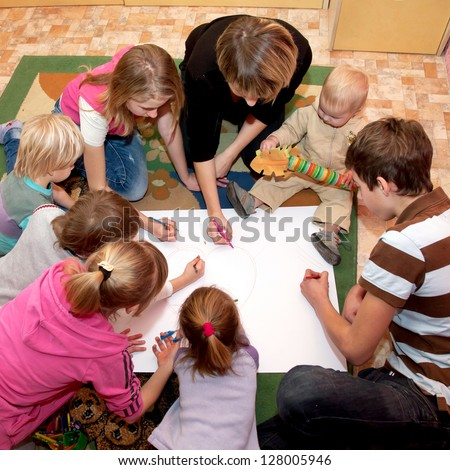 Big happy family - a mother and seven children drawing a heart together at home. Family concept. - stock photo