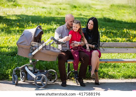 Big happy family: mother, father, older daughter, and little baby in baby carriage - stock photo