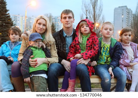 Big happy family of seven in the evening sitting on the bench. - stock photo