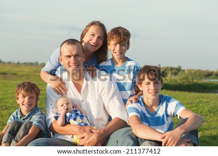 Big Happy Family. Parents with four children in countryside outdoors