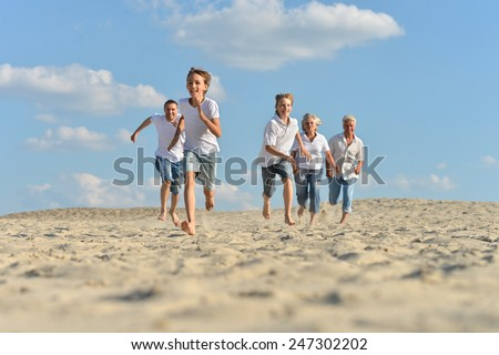 Big happy family running barefoot in the sand in the summer