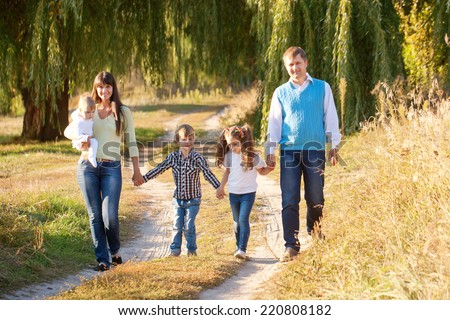 Big happy family walking along the path in the park. Father, mother, son, daughter and baby holding hands and going together. Family Ties concept. - stock photo