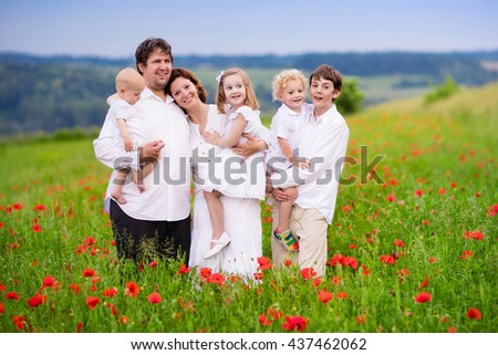 Big happy family with four children in red poppy flower field. Mother, father, toddler boy and girl, teenager son and little baby walking in summer meadow picking poppies. Kids pick flowers. - stock photo