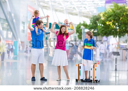 Big happy family with three kids traveling by airplane at Dusseldorf International airport, parents with teenager boy, toddler girl and little baby holding colorful luggage for summer beach vacation - stock photo