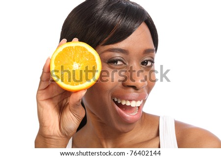 Big happy smile and excited fun pose with orange slice by beautiful young black woman. - stock photo