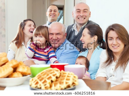 Big happy three generations family drinks tea with baked at home