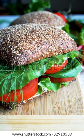 Big healthy rye bread sandwich with fresh tomatoes, green vegetables and herbs on a wooden kitchen board, blur black background, vertical - stock photo