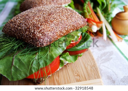 Big healthy rye bread sandwich with fresh tomatoes, green vegetables and herbs on a wooden kitchen board, blur background - stock photo