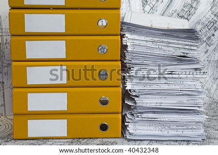 Big heap of design and project drawings in yellow folder on the table surface. Black-and-white whatman are background. - stock photo