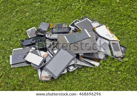 Big heap of the  broken and cracked  cellular telephones and  tablets lie on green lawn grass. Modern technologies pollute environment concept