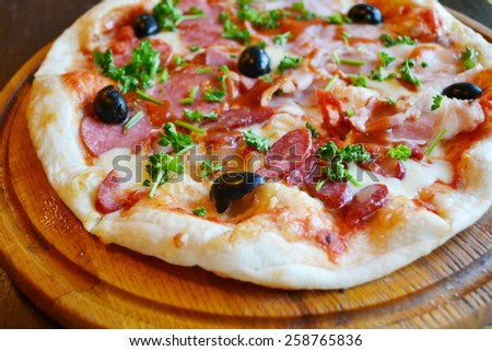 Big hot pizza with olives and salami - stock photo