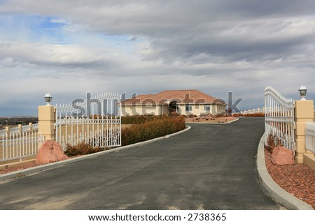 Big house with gated entrance under cloudy sky - stock photo