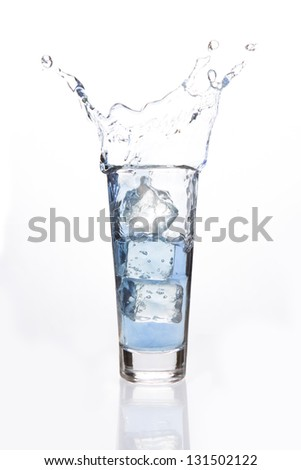 Big ice cubes falling in a filled glass on white background
