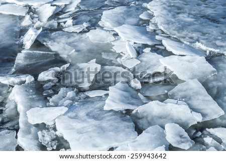 Big ice fragments covered with show on frozen river water. Dark blue natural background - stock photo