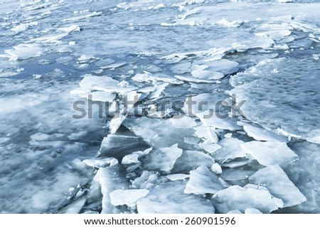 Big ice fragments covered with show on frozen river water. Dark blue nature background - stock photo
