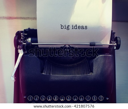 Big ideas message on a white background against womans hand typing on typewriter - stock photo