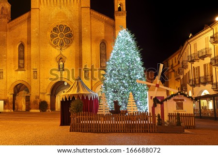Big illuminated Christmas tree on central square and San Lorenzo cathedral on background at evening in Alba, Northern Italy. - stock photo