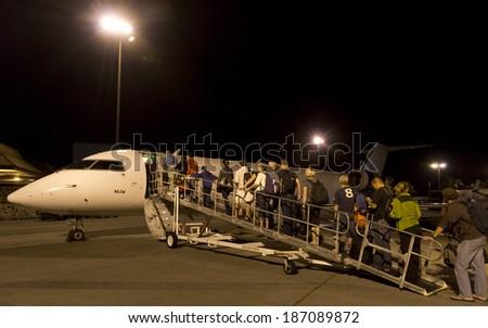 "BIG ISLAND, HAWAII - JANUARY 10, 2014: Passengers board a small ""island hopper"" flight from Kona to Honolulu on January 10, 2014.  Short flights run regularly between the different Hawaiian islands. - stock photo"