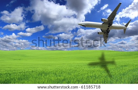 Big jet airplane flying above field - stock photo
