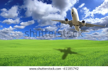 BIg jet airplane flying above green field - stock photo