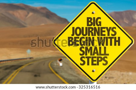 Big Journeys Begin With Small Steps sign on desert road - stock photo