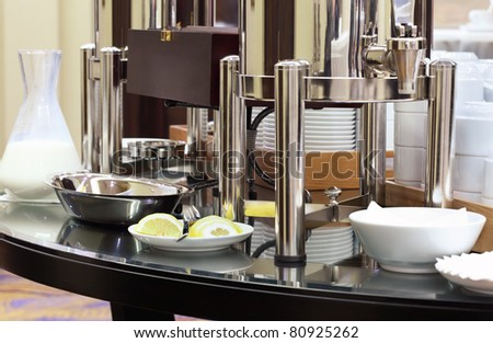 Big kettle-canister with tableware on stand-up party on conference - stock photo