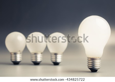 Big light bulb glowing with row of small light bulbs on background - stock photo