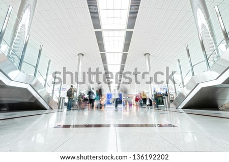 Big light hall in Dubai airport with passengers in hurry. United Arab Emirates. Modern style interior with shining metal constructions and lot of light. Travelling and tourism. - stock photo